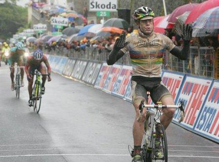 Cadel Evans cruza la línea de meta lleno de barro para ganar una etapa del Giro de Italia