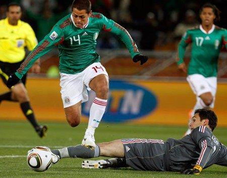 El delantero mexicano Hernández dribla al meta francés Lloris para lograr el primer gol de Mexico
