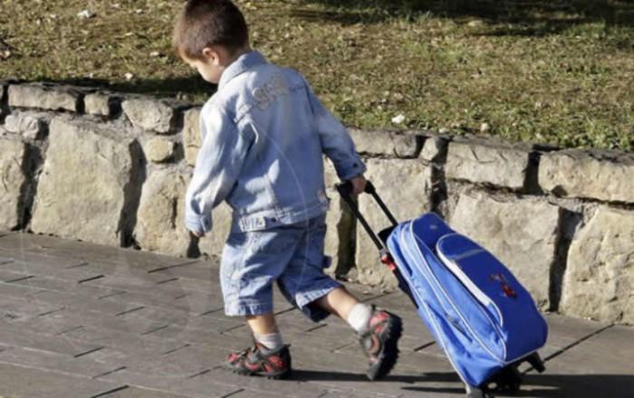 Niño al cole con mochila con ruedas