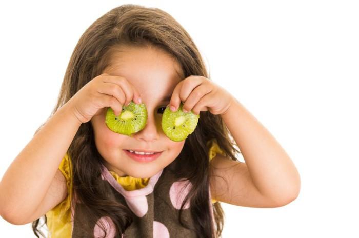 Niña comiendo kiwi