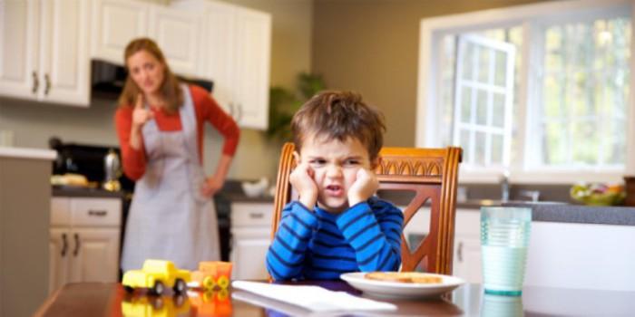 niño enfadado ante la mesa