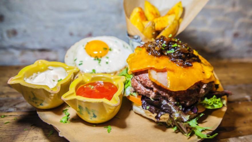Hamburguesa Madrileña 60 carne wagyu 40 nacional, queso guadarrameño macerado en cerveza, cebolla caramelizada, lechuga, pepinillos, huevos y bacon-Amargo place to be